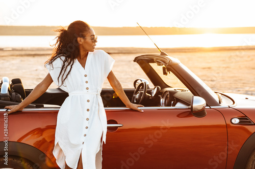 Fotografía  Photo of gorgeous african american woman standing by car on beach at sunrise