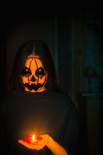 Frightening Pumpkin Face Character Hold A Candle. A Portrait Of A Halloween Creature