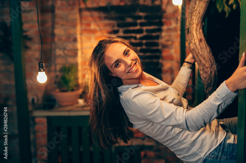 Valokuva  happy young female posing at home in backyard. evening scene