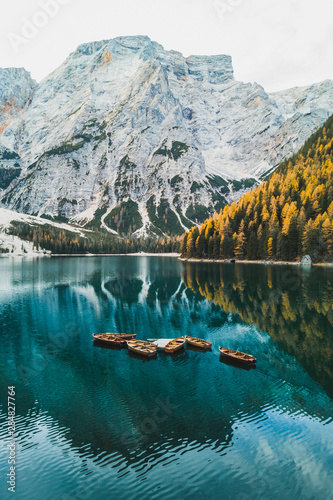 Foto op Aluminium Groen blauw Autumn landscape of Lago di Braies Lake in italian Dolomites mountains in northern Italy. Drone aerial photo with Wooden boats and beautiful reflection in calm water at sunrise. Pragser Wildsee