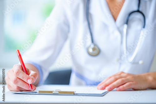 Cuadros en Lienzo A doctor with a stethoscope writing diagnosis and therapy of the disease in a clipboard during a medical consultation in hospital