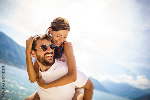 Handsome young man giving piggyback ride to girlfriend on beach Tableau sur Toile