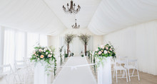 Indoor Wedding Ceremony With White Wedding Arch Decorated With Flowers And Big White Candles