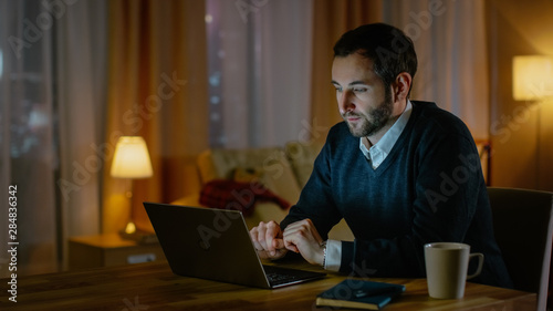 Respectable Looking Middle Aged Man Works on a Laptop from His House. His Apartment Has View on a Big City. Inside it's Warm and cosy.