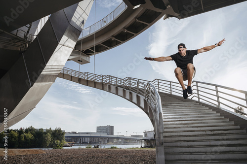 Fototapeta Parkour athlete doing a beautiful high jump from the stairs