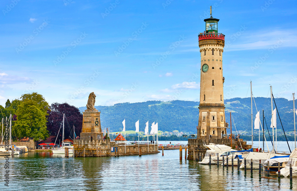 Fototapeta Lindau, Germany. Old lighthouse with clock in bay. Antique bavarian town at Lake Constance (Bodensee). Monument with statue of lion at entrance to port, yachts by piers. Summer landscape blue sky.