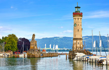 Lindau, Germany. Old Lighthouse With Clock In Bay. Antique Bavarian Town At Lake Constance (Bodensee). Monument With Statue Of Lion At Entrance To Port, Yachts By Piers. Summer Landscape Blue Sky.