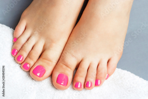 Pink pedicure close-up, isolated on a gray background, top view
