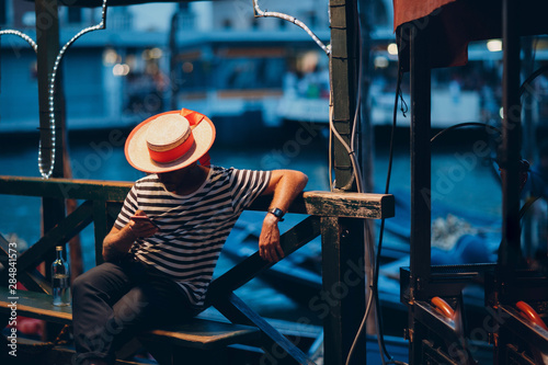 Fotografía Gondolier in  hat and striped clothes sits in  evening on canal and waits for cl