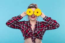 Close-up Positive Smiling Young Woman In A Red Checkered Shirt Holding Yellow Flowers On Her Eyes Posing Against A Blue Background. Concept Incognito And Fun.