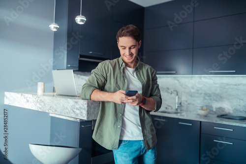 Fototapety, obrazy: Man standing in the kitchen and texting friend