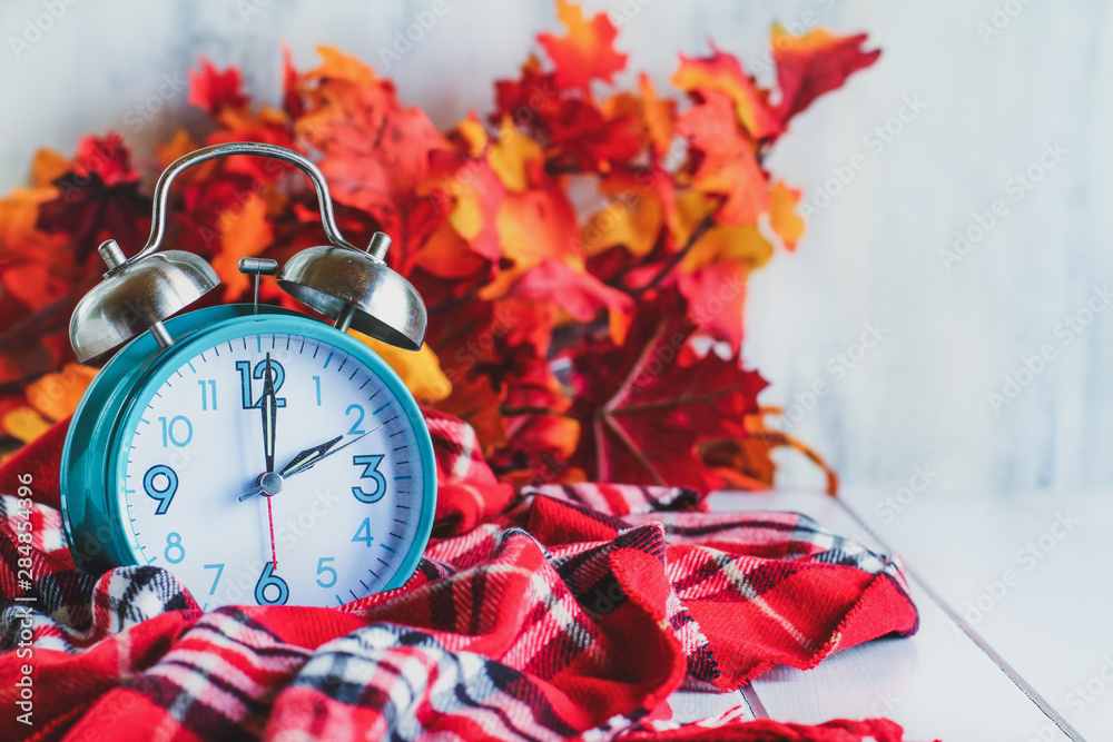 Fototapety, obrazy: Daylight savings time concept. Set your clocks back with this retro beautiful alarm clocks set to 2 am over rustic white background with red plaid scarf and autumn leaves. Free space for text.