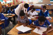 Teacher Helping Schoolchildren...