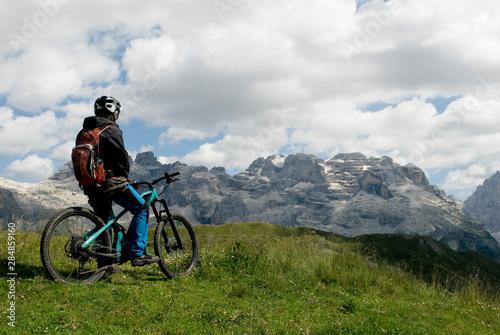Foto man with electric bike, e-bike, ebike, looking mountains of Brenta Peak, Grostè