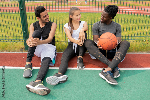 Two guys and girl in sportswear chatting while sitting on playground Fototapet