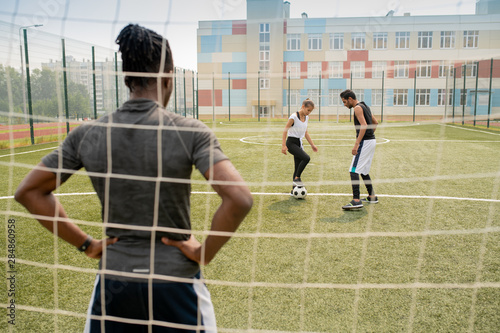 Fotografiet Rear view of young African sportsman standing by net and looking at two players