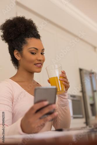 Beautiful woman having orange juice while using mobile phone at home