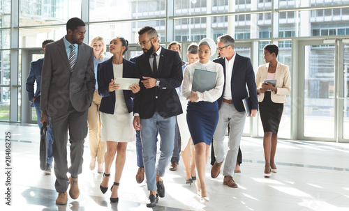 Front view of group of diverse business people walking together in lobby office
