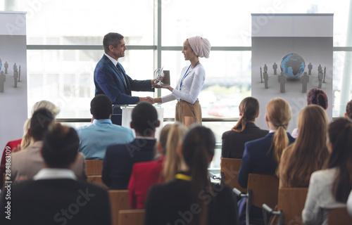 Fotografía  Businesswoman receiving award from businessman in a business seminar