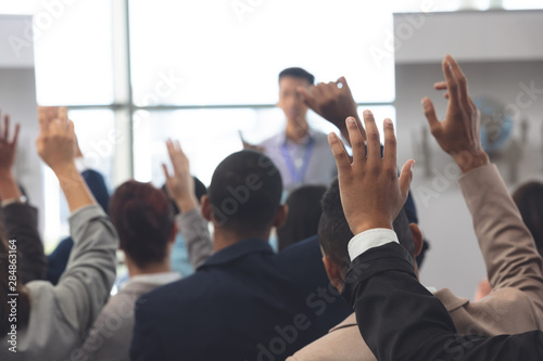 Fotografiet  Business people raising hands in a business seminar