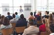 Businessman raising hand in a business seminar