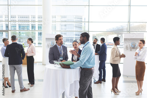 Business people discussing over documents at table during a seminar - 284863505