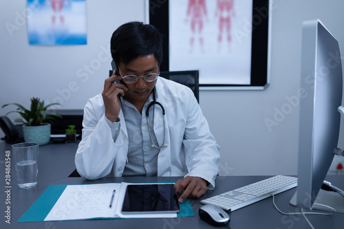 Fototapety, obrazy: Doctor talking on mobile phone while using digital tablet