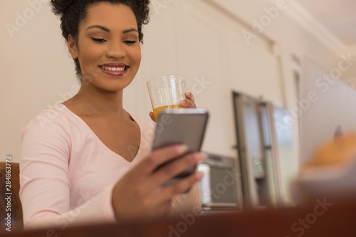 Woman having orange juice while using mobile phone at home