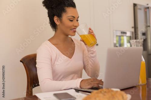 Woman having orange juice while using laptop at home