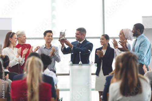 Businessman holding award at podium with colleagues in a business seminar Canvas Print