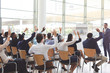 Group of business people raising hands at seminar at conference