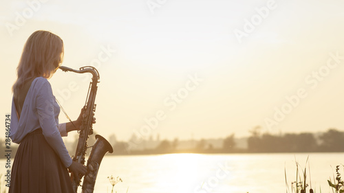 silhouette of a young beautiful girl playing the saxophone at sunrise by the river, a woman in a long dress on the nature at sunrise relaxing, concept music