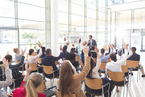 Fotografía  Business people listening to businessman and raising hands to ask him questions at conference