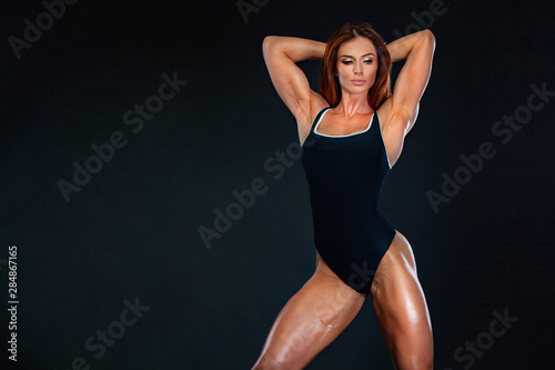 Obraz Beautiful fitness woman athlete and bodybuilder with perfect body wearing sport clothes for the gym training. Individual sports. Sports recreation. - fototapety do salonu