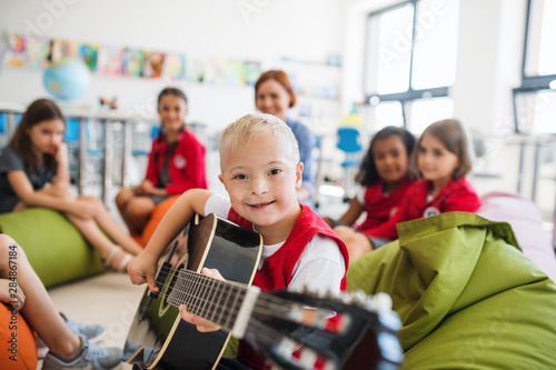 Fototapeta A down-syndrome boy with school kids and teacher sitting in class, playing guitar. obraz