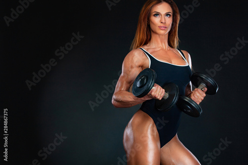Obraz Young fitness woman athlete and bodybuilder with dumbell. Individual sports. Sports recreation. - fototapety do salonu