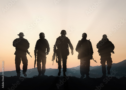 Photo Military silhouettes of soldiers against the backdrop of sunset sky