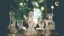 Set Of Vintage Crystal Glasses On The Black Tray With Christmas Decorations. Selective Focus