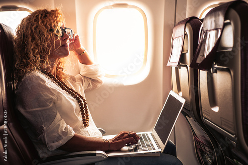 Fotografia  Business adult curly blonde woman travel on airplane connected to internet with