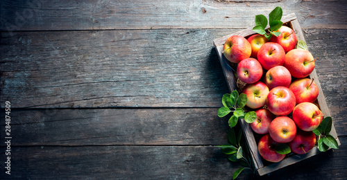 Ripe Apples In Wooden Basket On The Rustic Table - 284874509
