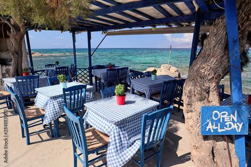 Fotografia Typical blue furniture Greek taverna by a turquoise Aegean Sea, Agios Prokopios,