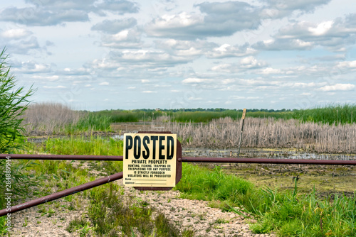 Yellow and black Private Property sign hangs on a fence in front of an open field Fototapeta