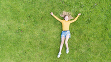Top View Of Young Girl Who Relaxing On The Grass.  Kid Lying In A Grass.