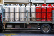 Truck With Gas Cylinders On The Road. Many Red And Gray Gas Cylinders Transported In Car.