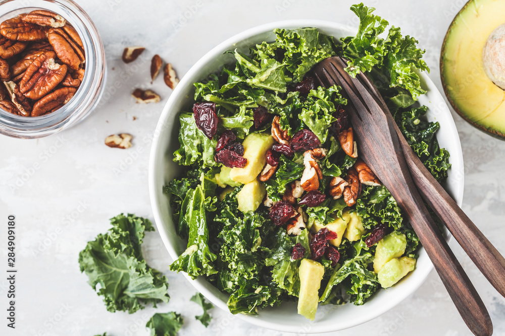 Fototapety, obrazy: Green kale salad with cranberries and avocado in white bowl, top view. Healthy vegan food concept.