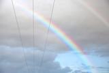 Fototapeta Tęcza - Kolorowa tęcza na tle chmór i przewodów elektrycznych.