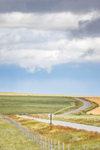 A Landscape Of A Road Passing Through Wheat Fields, Near Dupuyer, Central Montana, USA.