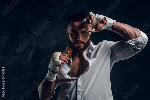 Photo Handsome brutal man in protective boxing gloves is vering mouth guard while posing for photographer
