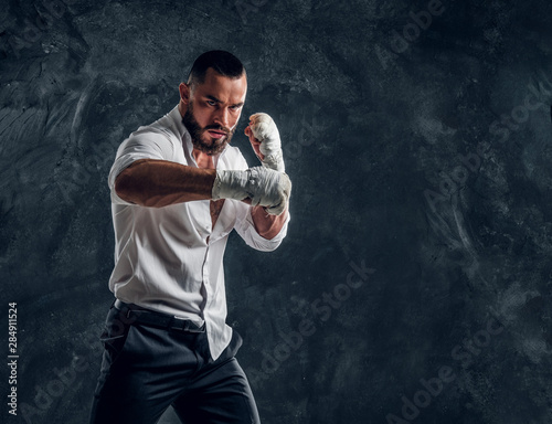 Agressive handsome man in white shirt is demonstraiting his punch at dark photo studio Wallpaper Mural