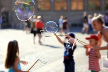 Dzieci puszczają kolorowe i ogromne bańki mydlane na rynku miasta.
